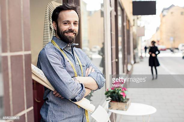 Portrait of confident mid adult male designer standing arms crossed outside studio