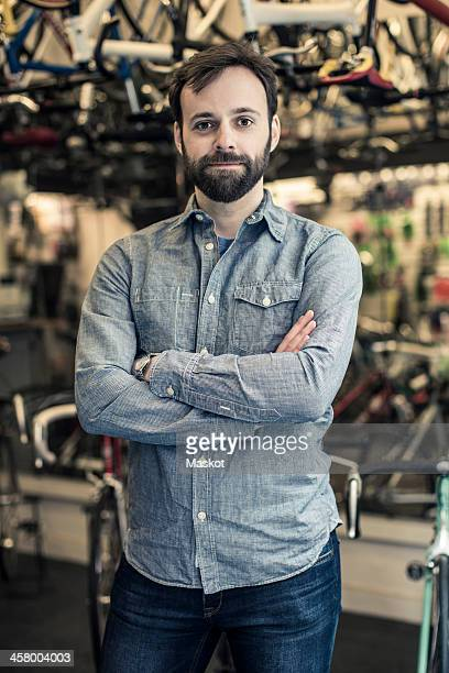 Portrait of confident mid adult male owner standing arms crossed at bicycle repair shop