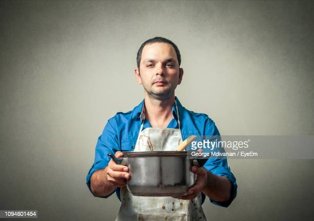 portrait of confident mid adult man holding cooking pot against gray background - mid volwassen mannen stockfoto's en -beelden