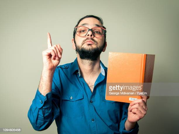 portrait of confident mid adult man pointing upwards while holding book against gray background - index finger stock pictures, royalty-free photos & images