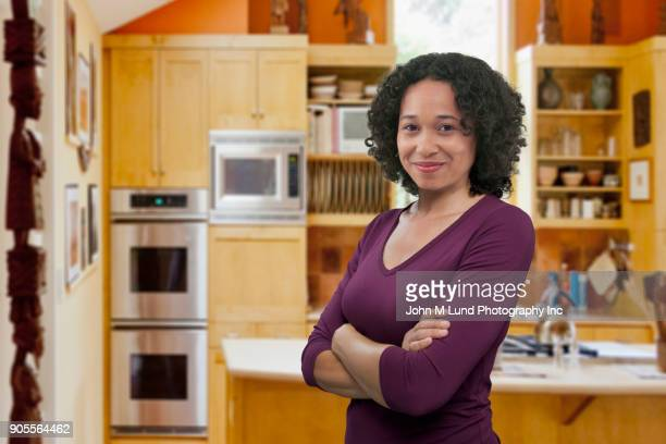 Portrait of confident mixed race woman in domestic kitchen