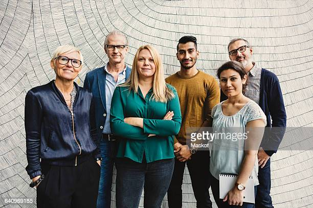portrait of confident multi-ethnic business people standing against wall in office - middelgrote groep mensen stockfoto's en -beelden