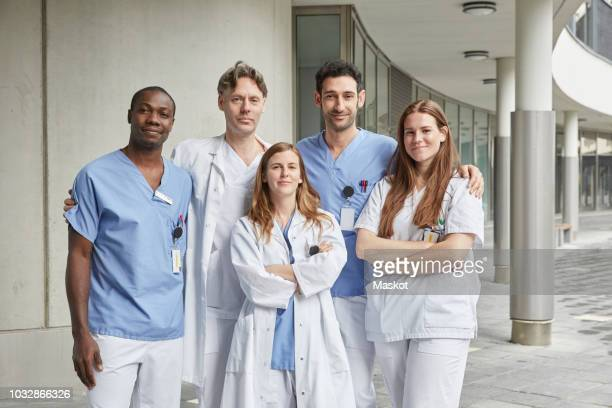 portrait of confident multi-ethnic healthcare workers standing at hospital - group of doctors stock pictures, royalty-free photos & images
