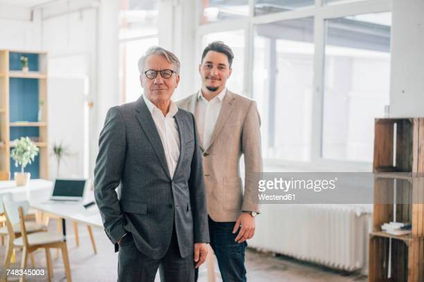 portrait of confident old and young businessman in office - sohn stock-fotos und bilder