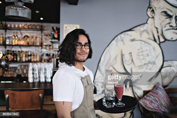 portrait of confident owner holding drink in serving tray at restaurant - male likeness stock pictures, royalty-free photos & images