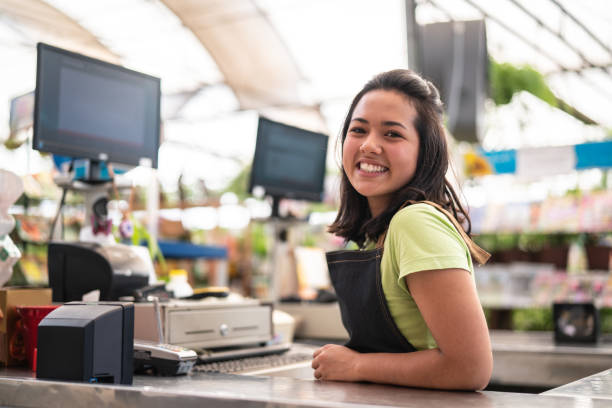 portrait of confident owner leaning on checkout counter at flower shop - asian woman cashier stock pictures, royalty-free photos & images