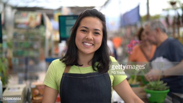 portrait of confident owner leaning on checkout counter at flower shop - assistant stock pictures, royalty-free photos & images