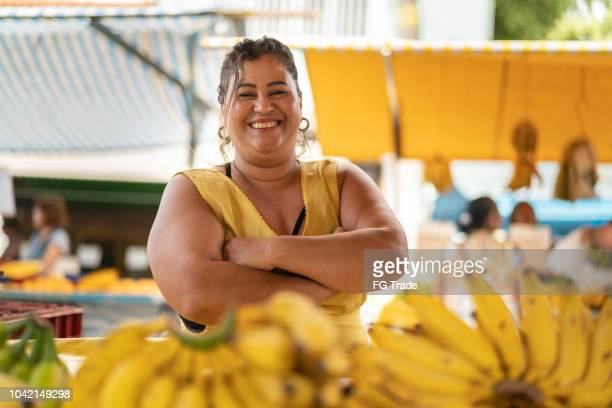 portrait of confident owner - selling bananas at farmers market - brazil stock pictures, royalty-free photos & images