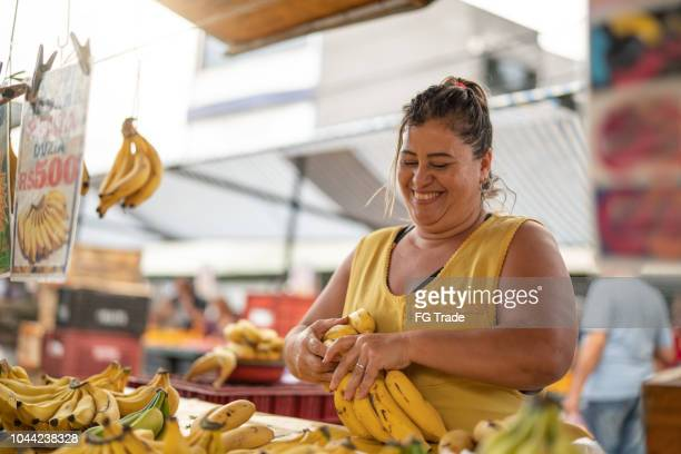 portrait of confident owner - selling bananas at farmers market - market vendor stock pictures, royalty-free photos & images