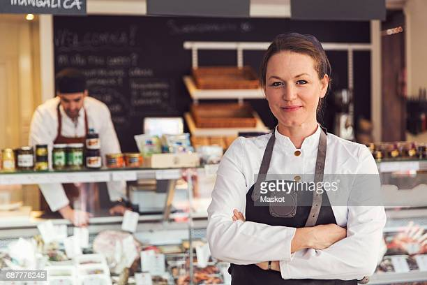 portrait of confident owner standing arms crossed while colleague working in background at grocery store - delicatessen stock pictures, royalty-free photos & images