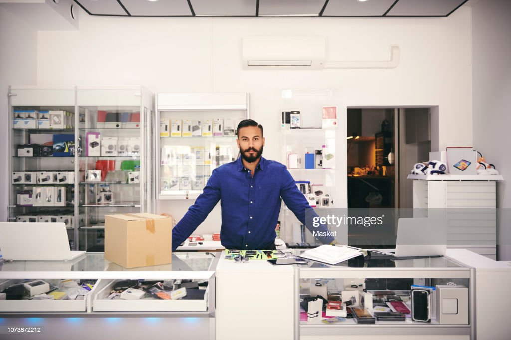 Portrait of confident owner standing at counter in electronics store : Stock Photo
