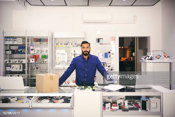 portrait of confident owner standing at counter in electronics store - assistant stock pictures, royalty-free photos & images