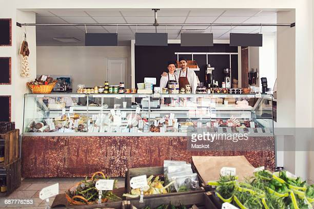 Portrait of confident owners standing in grocery store