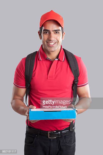 Portrait of confident pizza delivery man against gray background