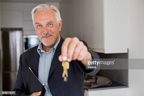 Portrait of confident real estate agent holding new house keys