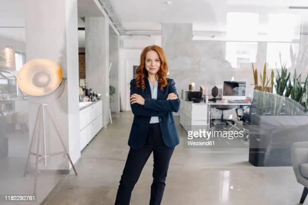 portrait of confident redheaded businesswoman standing in office - anzugjacke stock-fotos und bilder