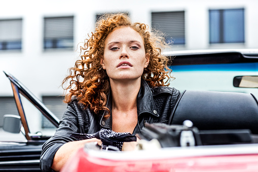 Portrait of confident redheaded woman in sports car - gettyimageskorea