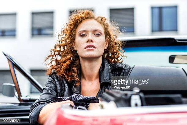 portrait of confident redheaded woman in sports car - unabhängigkeit stock-fotos und bilder