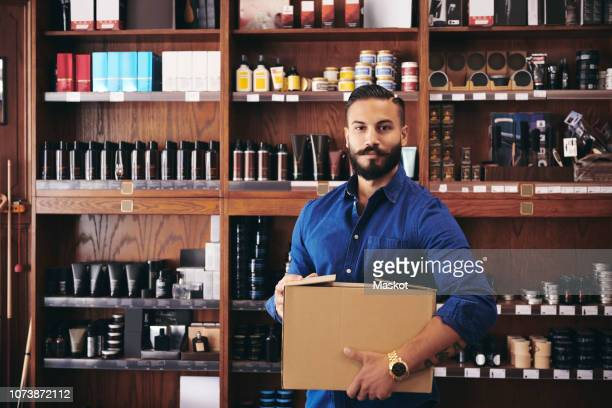 portrait of confident salesman carrying box while standing against rack in deli - window display stock photos and pictures