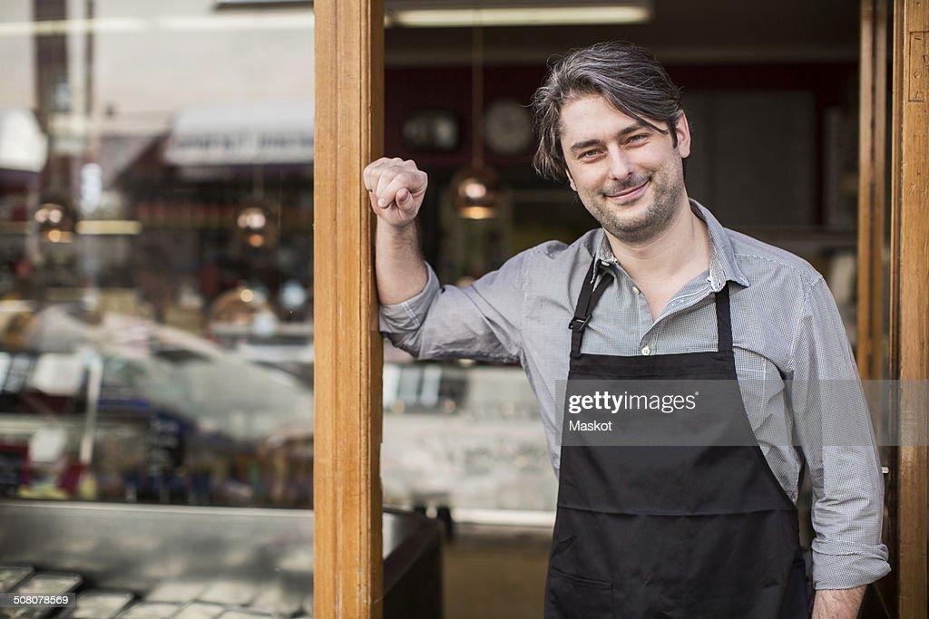 Portrait of confident salesman standing at supermarket entrance : Stock Photo