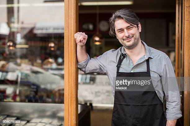 portrait of confident salesman standing at supermarket entrance - delicatessen stock pictures, royalty-free photos & images