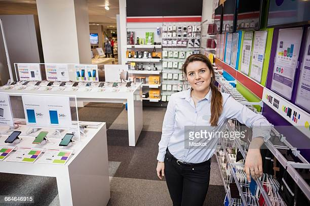 portrait of confident saleswoman standing in store - electronics store stock photos and pictures