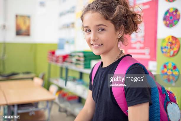 Portrait of confident schoolgirl in classroom
