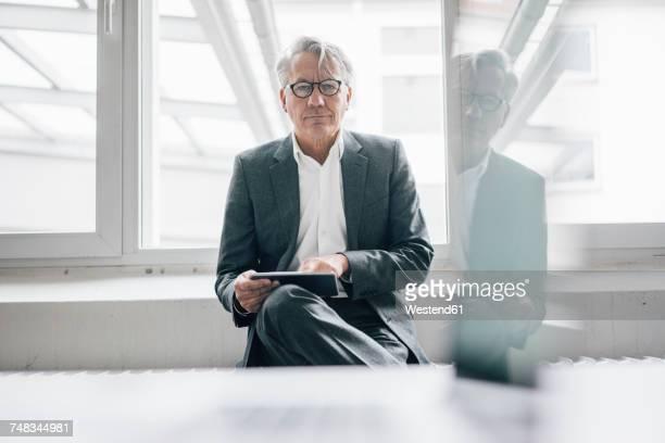 Portrait of confident senior businessman using tablet