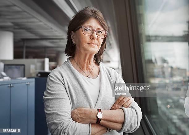 portrait of confident senior businesswoman standing arms crossed by window in office - frau 65 jahre stock-fotos und bilder
