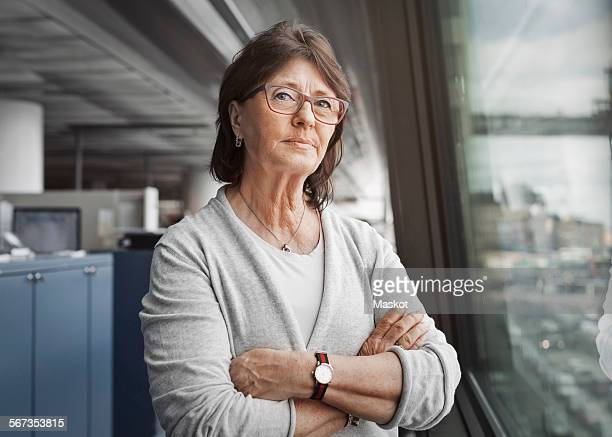 portrait of confident senior businesswoman standing arms crossed by window in office - 65 69 anni foto e immagini stock