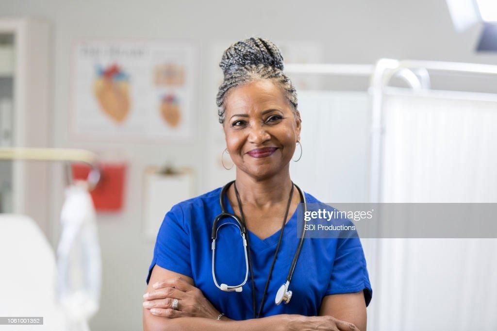 Portret van vertrouwen senior vrouwelijke arts in scrubs : Stockfoto