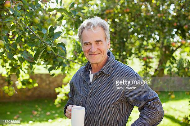 retrato de confianza senior hombre bebiendo café en orchard - 60 64 años fotografías e imágenes de stock