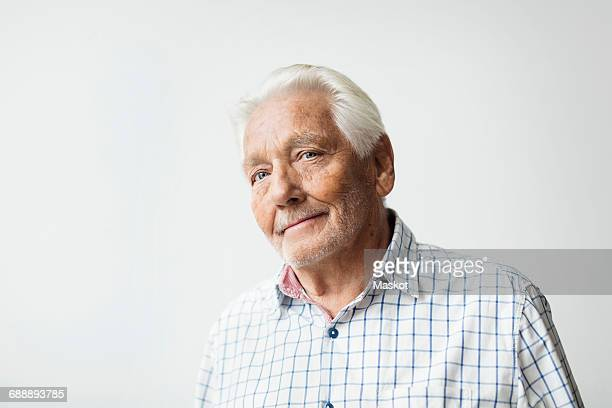 Portrait of confident senior man smiling against white background