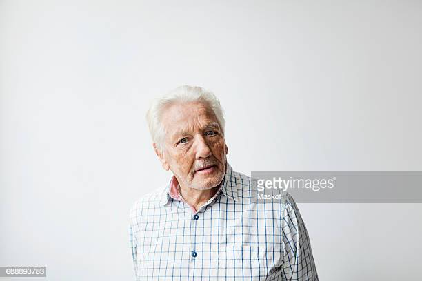 Portrait of confident senior man standing against white background