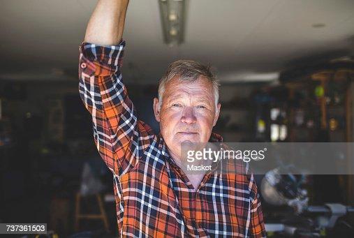 Portrait of confident senior man standing in workshop