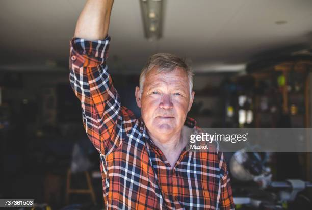 portrait of confident senior man standing in workshop - senior stock-fotos und bilder