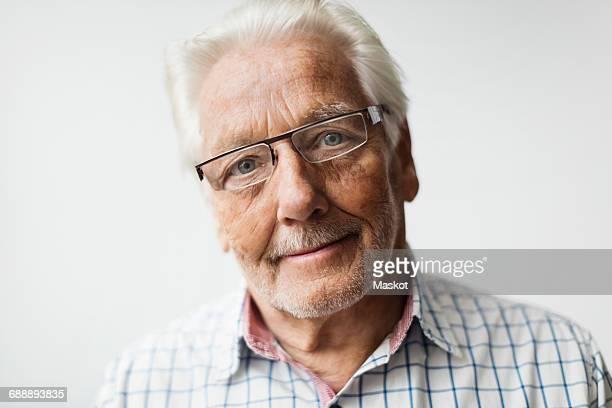 Portrait of confident senior man wearing eyeglasses against white background
