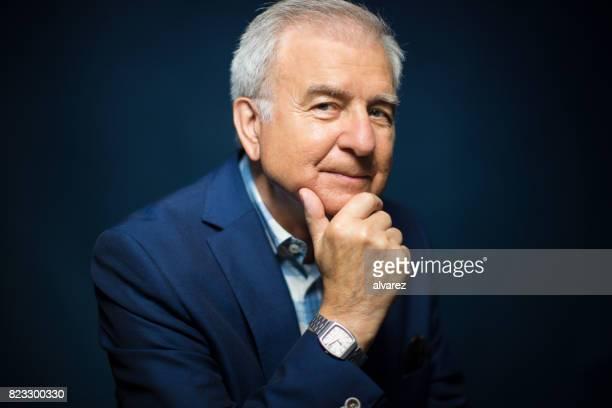Portrait von zuversichtlich Senior Mann mit Hand am Kinn