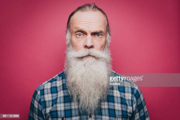 portrait of confident senior man with long white beard over pink background - long hair stock pictures, royalty-free photos & images
