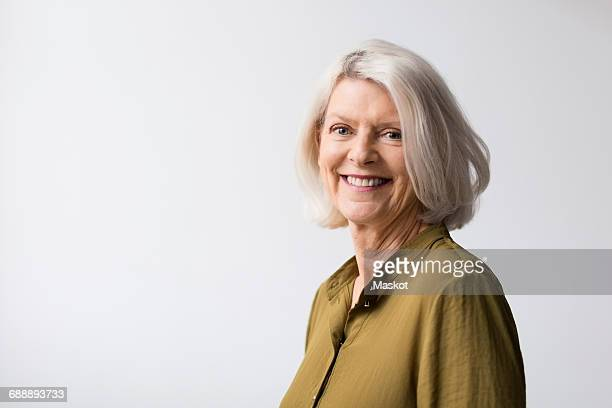 Portrait of confident senior woman against white background