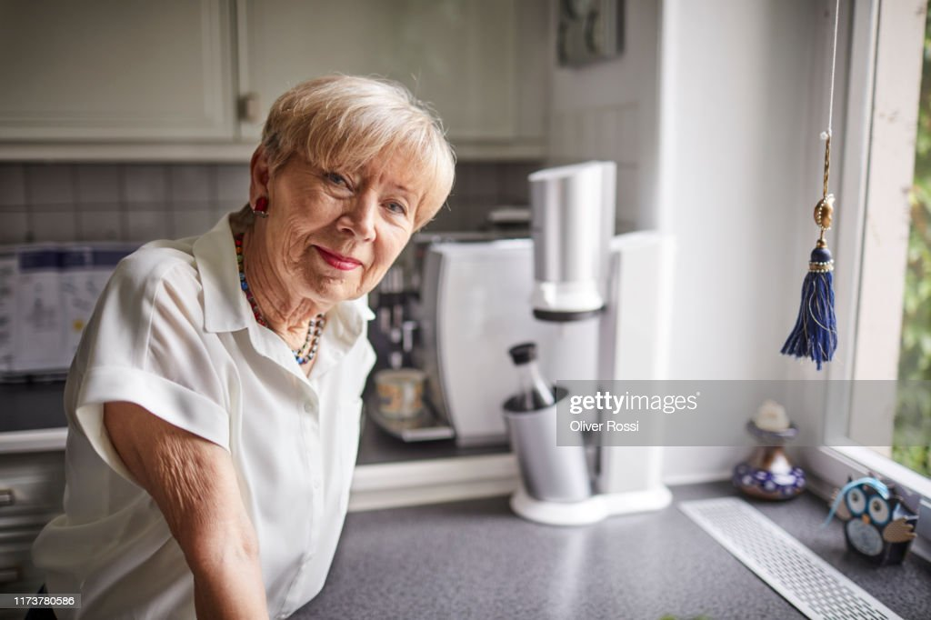 Portrait of confident senior woman in kitchen at home : Stock Photo