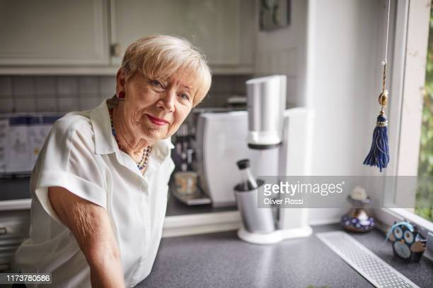 portrait of confident senior woman in kitchen at home - senior women stock pictures, royalty-free photos & images