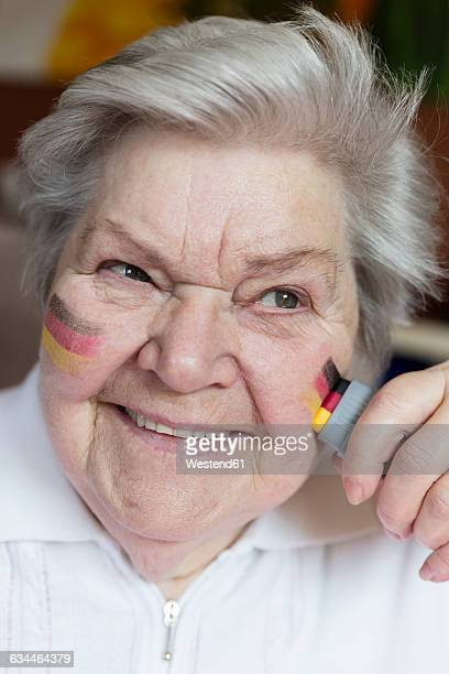 Portrait of confident senior woman painting German national colors on her cheek