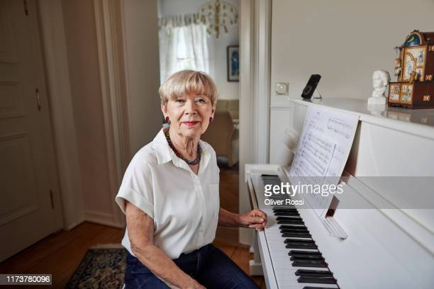portrait of confident senior woman sitting at the piano at home - musician stock pictures, royalty-free photos & images