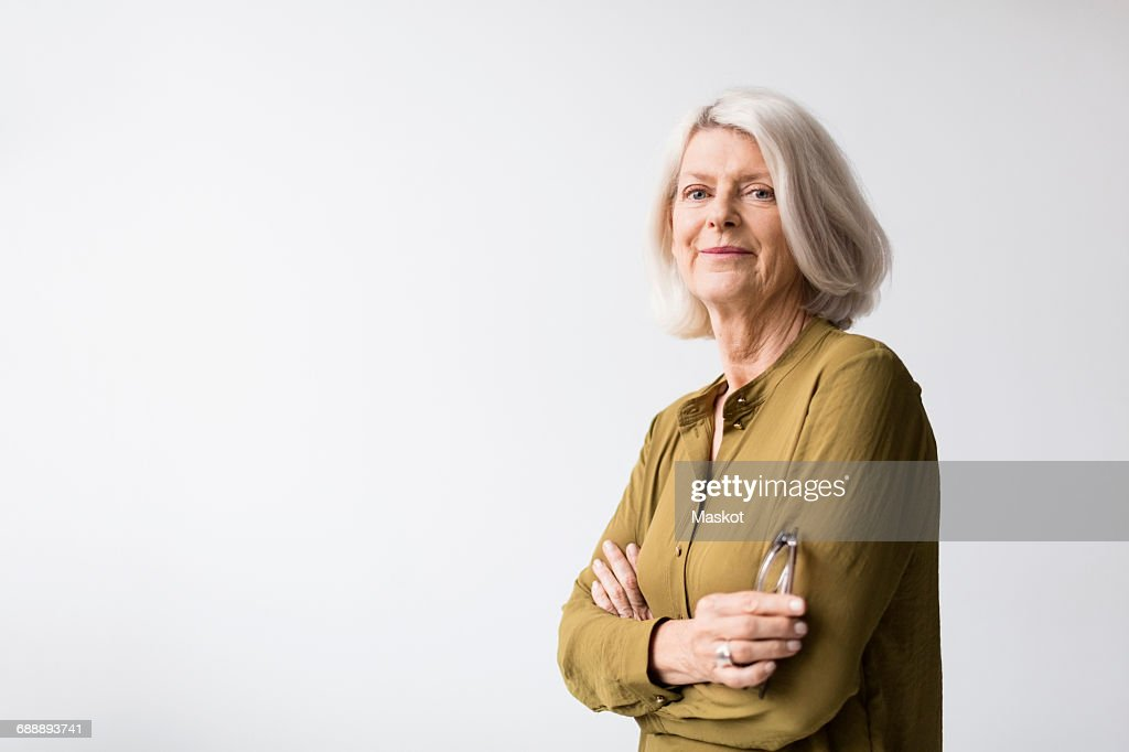 Portrait of confident senior woman standing arms crossed against white background : Stock-Foto
