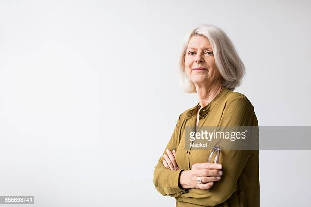 portrait of confident senior woman standing arms crossed against white background - waist up stock pictures, royalty-free photos & images
