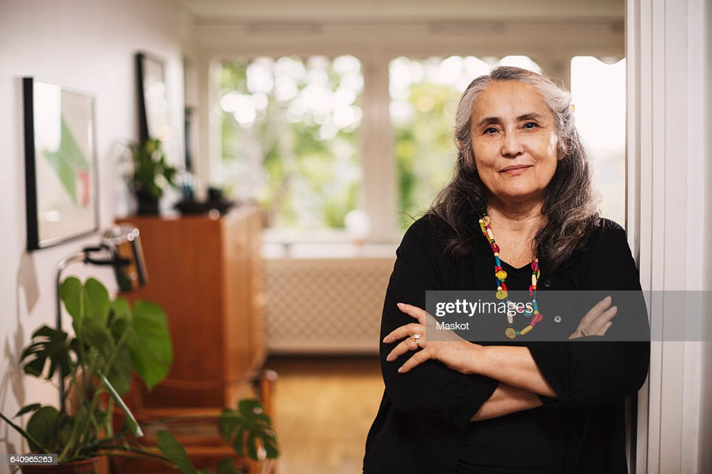 Portrait of confident senior woman standing arms crossed at home : Stock Photo