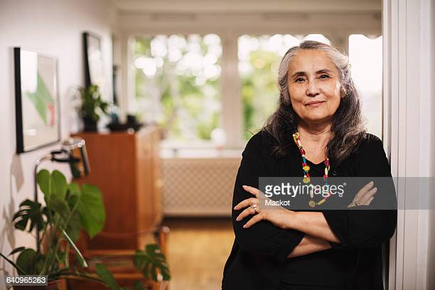 portrait of confident senior woman standing arms crossed at home - home icon stock photos and pictures