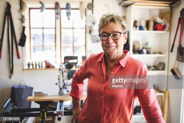 Portrait of confident senior woman standing in workshop