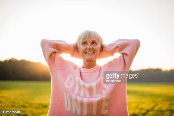 portrait of confident senior woman standing on rural meadow at sunset - frauenpower stock-fotos und bilder